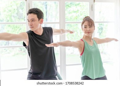young asian couple exercising in living room