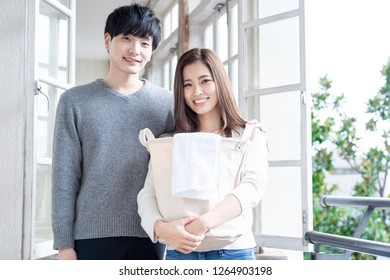 young asian couple hanging the laundly