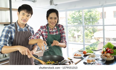Young Asian couple are happy to cook together, two families are helping each other prepare to cook in the kitchen.