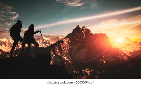 Young asian couple hikers climbing up on the peak of himalaya mountains. People helping each other hike up a mountain at sunrise. Giving a helping hand. Climbing ,Helps and team work concept