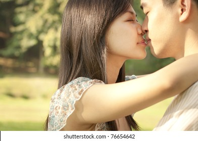 Young Asian couple kissing at outdoor