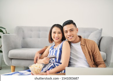Young Asian couple loking at laptop screen to buy online or watching movie at home