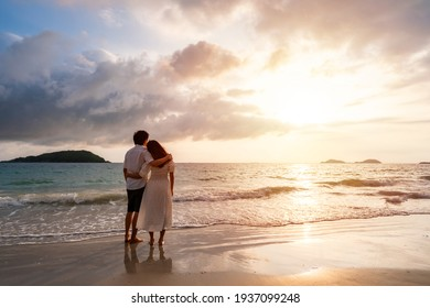 Young asian couple looking beautiful sunset on the tranquil beach, Summer vacation concept