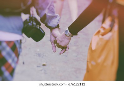 Young asian couple in love walking in the park holding hands on vintage tone . Couples holding hands. We will love and take care of you forever concept.