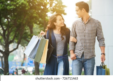 Young Asian couple in love walking in the city after shopping