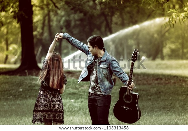 Young asian couple in love walking in the park holding hands together with other hand hold guitar on sunny day, color filter effect.