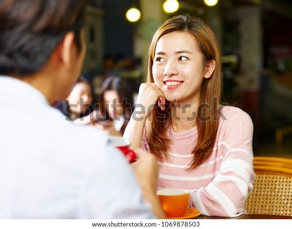 喫茶店で顔を合わせて話し合いながら、テーブルで座っている若いアジア人カップルの恋人。