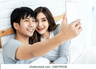 Young asian couple lying on bed and taking selfie by smartphone. Asian lovers take a photo with toothy smile. Happy lover hug each other and smiling on bed at home. Lover and romance concept.