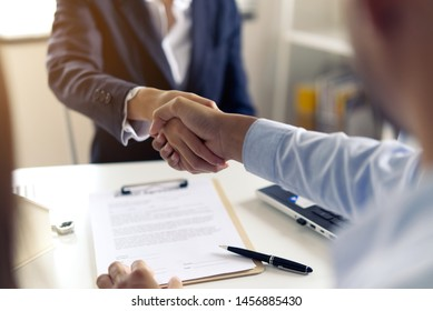 Young Asian couple making contract with house sale agency. Man shaking hand with female agent sitting opposite and his wife sitting next to him with smile looking at house broker. Real estate concept.
