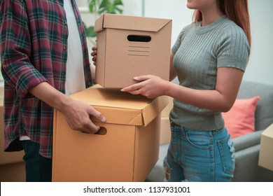Young Asian couple packing their belonging into cardboard box before moving to new resident or house after buy or rent a new one.