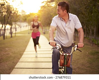 young asian couple running, riding bike outdoors in park at sunset, fitness, sport and exercise, healthy life and lifestyle concept.