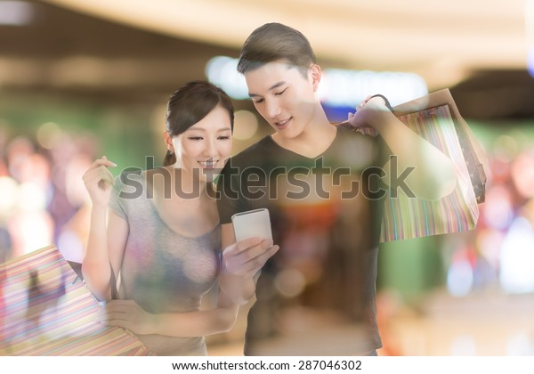 Young Asian couple shopping and looking at cellphone in the mall