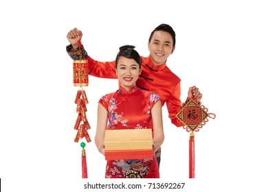 Young Asian couple showing Tet decorations, isolated on white