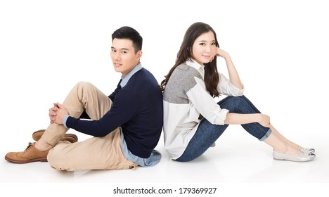 Young Asian couple sit on ground back to back on studio white background.