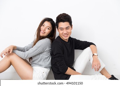 Young Asian Couple Sitting Back to Back