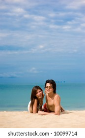 A young Asian couple sitting on beach with ocean behind