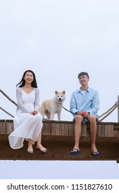 Young asian couple sitting on pier with pet dog.
