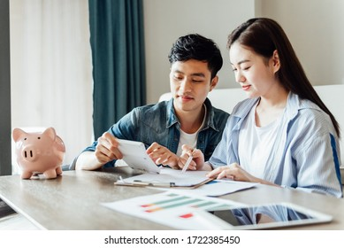 A young asian couple is sitting on a carpet using a computer - Shutterstock ID 1722385450