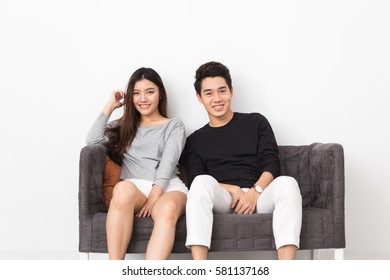 Young Asian couple sitting on the couch