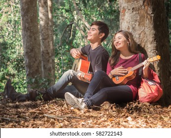 Young asian couple sitting at tree playing ukulele/guitar and sing a song chilling at forest nature during traveling outdoor camping/trekking with happy feeling/relaxing concept