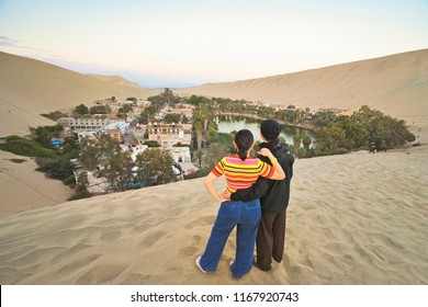 A young asian couple stand on the desert and enjoy the view of Huacachina, Ica, Peru.