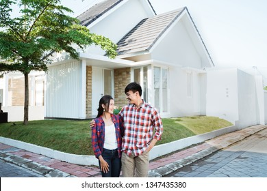 young asian couple standing in front of their new house and smiling