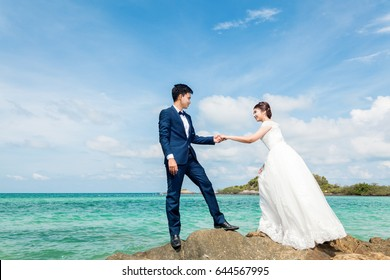 Young asian couple in sweet moment,groom and bride romantic at beautiful sea and blue sky