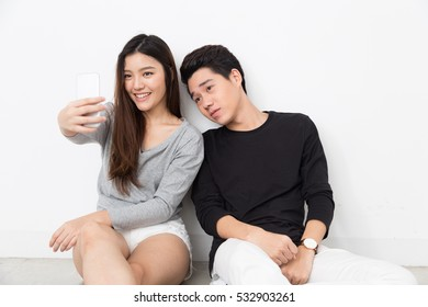 Young Asian couple taking selfie