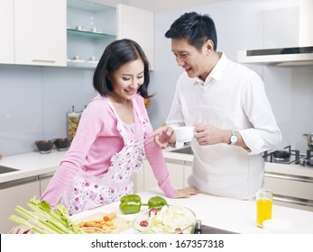young asian couple talking in kitchen.