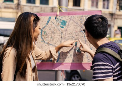 Young Asian couple tourist looking at city map and directions together in Bangkok, Thailand