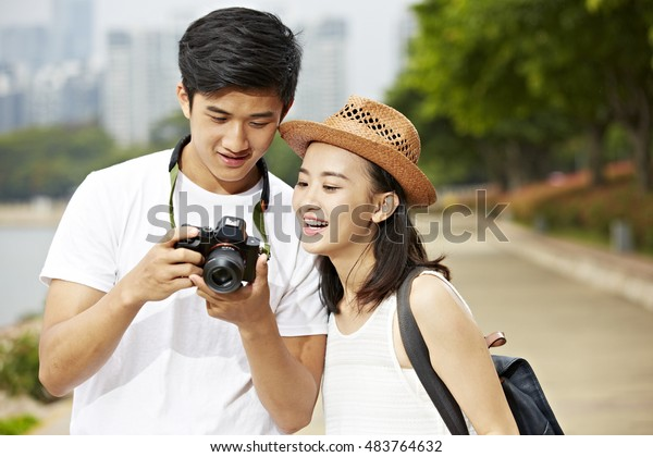 young asian couple tourists looking at camera's monitor checking pictures taken