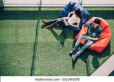 Young Asian couple using laptop notebook and digital tablet together in modern public park, sit on bean bag, top view with copy space on grass. Information technology gadget or casual business concept