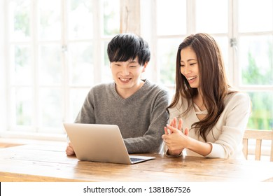 young asian couple using laptop computer in living room