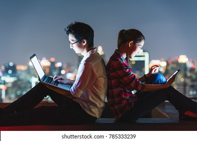 Young Asian couple using laptop and smartphone together, lean on each other back to back. Rooftop night scene with city view background. Modern technology lifestyle or internet gadget devices concept