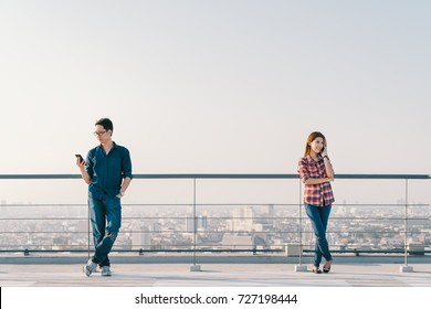 Young Asian couple using telephone call and smartphone together on building roof. Mobile cellphone device or information technology telecommunication concept. Cityscape view background, sky copy space