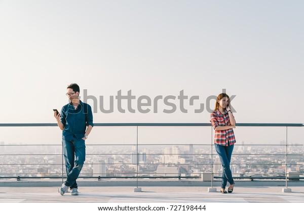 アジアの若い夫婦が電話とスマートフォンを使って屋根を作る。携帯電話装置または情報技術通信のコンセプト。都市の景観ビューの背景、空のコピースペース