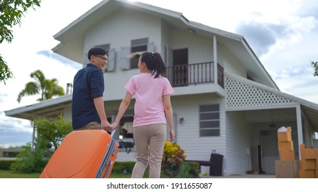 Young asian couple walking in to front of their new house