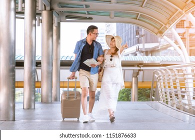 Young asian couple walking with luggage travel summer vacation or honeymoon trip