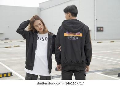 Young Asian couple walking on the street, fashion,  wearing coats