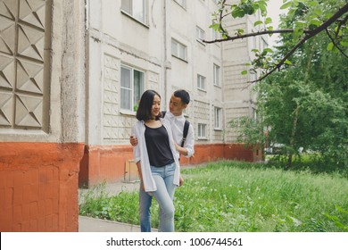 young Asian couple walks in the city Park. emotional portrait of students. young girl and guy brunette having fun on Valentine's day. concept: 14 February