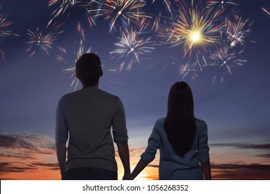 Young asian couple watching spectacular fireworks on the sky