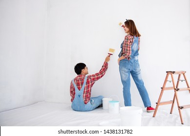 young asian couple in yom-bear and plaids shirts in concept couple help painting a new color the room renovation in Thailand
