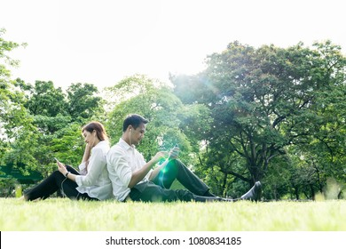Young asian couple,lover holding earphone,smartphone sit relax in park,tree background copy space. Happy outdoor on summer,spring sunshine in city green park,garden lifestyle. Take a break after work.