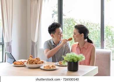 Young Asian Couples eating fried chicken together in living room of contemporary house for modern lifestyle concept