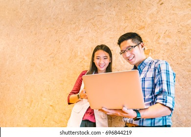 Young Asian coworker or college student team using laptop computer together at office or campus. Happy casual business talk, information technology, or e-learning education concept. With copy space