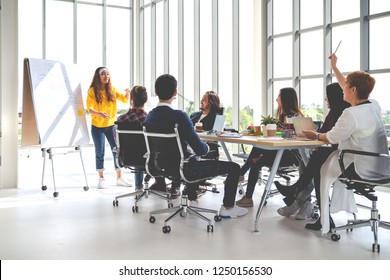 Young asian creative hipster female leader standing and making presentation at modern office happy talking marketing idea with team. Casual asian people business meeting workshop soft tone concept.