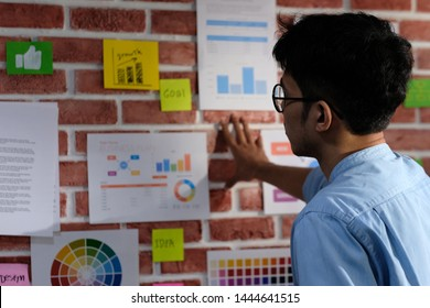 Young asian creative man reading and thinking about paper work ideas on office wall with concentration, working occupation lifestyle