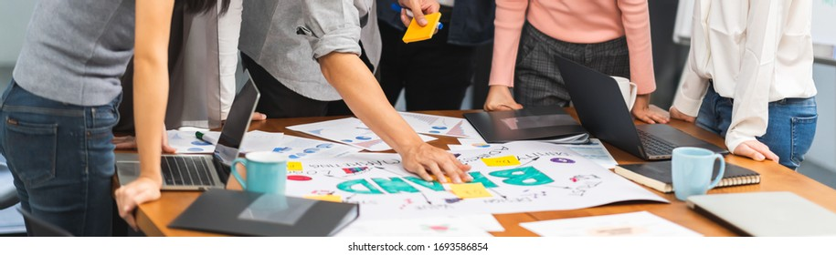 Young Asian creative team work together in business brand design project brainstorm meeting. Modern office, colleague coworker, marketing advertisement research or people teamwork concept. Banner size