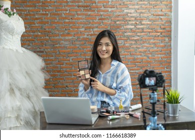 Young Asian cute artist woman beauty vlogger or blogger doing a cosmetic makeup tutorial vlog with brushes looking camera, recording viral clip to share on social media live streaming for Internet