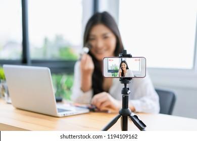 Junge süße Künstlerin in Asien Schönheitvloggerin oder Bloggerin, die eine kosmetische Make-up-Tutorial-Vlog mit Bürsten aussehen Kamera Smartphone, die Aufnahme virale Video-Aktie in sozialen Medien Live-Streaming Internet